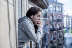 Junge schöne lateinische Frau, die traurig und auf einem Balkon in einem Krisenkonzept deprimiert schaut Lizenzfreies Stockfoto