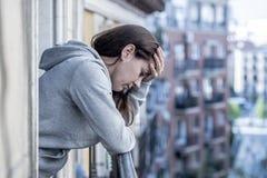 Junge schöne lateinische Frau, die traurig und auf einem Balkon in einem Krisenkonzept deprimiert schaut Lizenzfreie Stockbilder