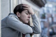 Junge schöne lateinische Frau, die traurig und auf einem Balkon in einem Krisenkonzept deprimiert schaut Stockfotos