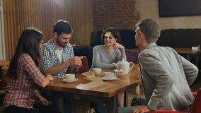 Junge schöne Leute am Café verlegen das Spielen des Namenspiels mit den Aufkleberanmerkungen, die zu ihrer Stirn sticked sind lizenzfreies stockfoto