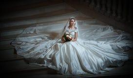 Junge schöne luxuriöse Frau im Hochzeitskleid, das auf Treppe sitzt, tritt in Halbdunkel Braut mit enormem Hochzeitskleid Lizenzfreie Stockfotos