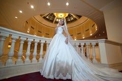 Junge schöne luxuriöse Frau im Hochzeitskleid, das im luxuriösen Innenraum aufwirft Braut mit enormem Hochzeitskleid im majestäti Stockfoto
