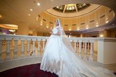 Junge schöne luxuriöse Frau im Hochzeitskleid, das im luxuriösen Innenraum aufwirft Braut mit enormem Hochzeitskleid im majestäti Lizenzfreies Stockbild