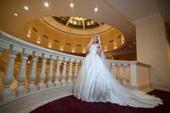 Junge schöne luxuriöse Frau im Hochzeitskleid, das im luxuriösen Innenraum aufwirft Braut mit enormem Hochzeitskleid im majestäti Lizenzfreies Stockfoto