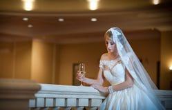 Junge schöne luxuriöse Frau im Hochzeitskleid, das im luxuriösen Innenraum aufwirft Braut mit enormem Hochzeitskleid im majestäti Stockfotografie