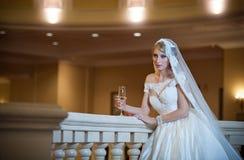 Junge schöne luxuriöse Frau im Hochzeitskleid, das im luxuriösen Innenraum aufwirft Braut mit enormem Hochzeitskleid im majestäti Lizenzfreie Stockbilder
