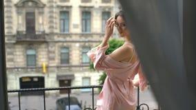 Junge schöne Mädchenbraut in einem peignoir, das auf dem Balkon übersieht die alte Stadt und wartet auf den Bräutigam steht stock video footage