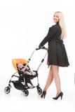 Junge schöne Mama mit Baby im Spaziergänger schönes blondes schlenderndes Kleinkind und Lächeln Lizenzfreie Stockbilder
