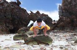 Junge schöne Mannmeditation auf Strand Lizenzfreie Stockfotos