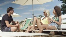 Junge schöne Mischrassefreunde, die auf sunbeds unter Regenschirm sitzen und Ferien genießen Stockfoto