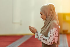 Junge schöne moslemische Frau, die in der Moschee betet stockfotografie