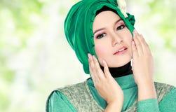 Junge schöne moslemische Frau mit grünes Kostüm tragendem hijab Stockfoto