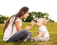 Junge schöne Mutter, die draußen ihr Babypüree im Sonnenlicht einzieht lizenzfreie stockfotos