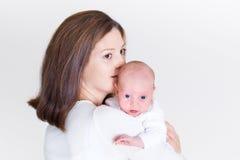 Junge schöne Mutter, die ihr neugeborenes Baby küsst Stockbild