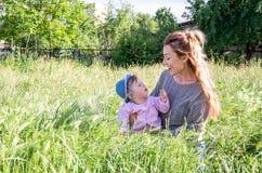 Junge schöne Mutter, die im Gras mit ihrer kleinen Babytochter in Panama spielt Lizenzfreie Stockbilder
