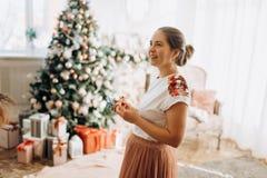 Junge schöne Mutter hält die Dekorationen des neuen Jahres, die im vollen des hellen gemütlichen Raumes nahe bei dem Baum des  stockfoto