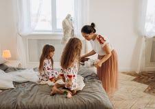 Junge schöne Mutter holt ihren Töchtern Kakao mit Eibischen und Plätzchen, die auf dem Bett im vollen sitzen lizenzfreie stockfotos