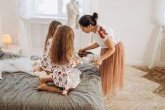 Junge schöne Mutter holt ihren Töchtern Kakao mit Eibischen und Plätzchen, die auf dem Bett im vollen sitzen stockfoto