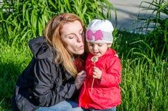 Junge schöne Mutter mit entzückendem kleinem Tochter Baby mit langen Haar Europäern in einer Wiese mit Gras und Blumen, plucke Stockbild