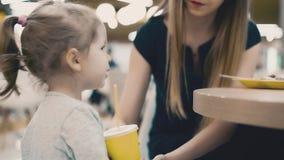 Junge schöne Mutter mit ihrer kleinen Tochter, die in einem Café sitzt Mutter gibt ihr Babygetränk durch das Stroh, unterrichtet  stock video footage