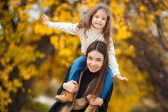 Junge schöne Mutter mit ihrer kleinen Tochter in Herbst Park Stockfoto