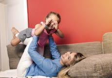 Junge schöne Mutter, Spaß mit ihrer kleinen Tochter habend stockbild