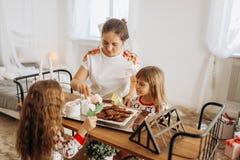 Junge schöne Mutter und ihre zwei bezaubernden kleinen Töchter sitzen stockbilder