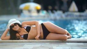 Junge schöne nette Brunettefrauen, die nahe dem Swimmingpool aufwerfen stock footage