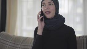 Junge schöne Ostfrau in der schwarzen Kleidung und im schönen Kopfschmuck nennend durch Handy Junge asiatische Moslems stock video footage