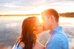Junge schöne Paare in der Liebe, die auf dem Strand auf Sonnenuntergang bleibt und küsst Weiche sonnige Farben Stockbild