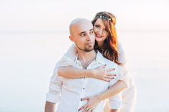 Junge schöne Paare in der Liebe am sonnigen Abend des Sommers auf dem Meer Lizenzfreies Stockbild