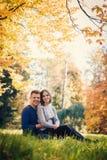 Junge schöne Paare, die auf dem Gras sitzen lizenzfreie stockfotografie