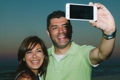 Junge schöne Paare, die auf dem Strand lächeln Stockfotos
