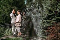 Junge schöne Paare, die in den Park und in die Stände auf der Brücke gehen Stockfotografie