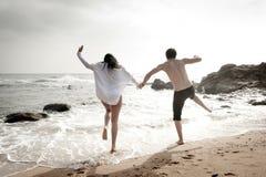 Junge schöne Paare, die den Spaß springt entlang Strand haben Lizenzfreies Stockbild