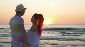 Junge schöne Paare, die in der Dämmerung auf einem Strand küssen stock footage