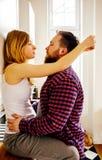 Junge schöne Paare, die in der Küche küssen Stockbild