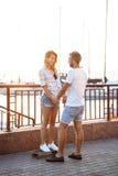 Junge schöne Paare, die an der Küste, lächelnd gehen und fahren Skateboard Stockfotografie