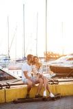 Junge schöne Paare, die an der Küste, lächelnd sitzen und fahren Skateboard Lizenzfreie Stockbilder