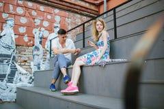 Junge schöne Paare, die draußen Schach in der Stadt spielen Stockfoto