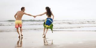 Junge schöne Paare, die entlang Strand mit Brasilien-Flagge laufen Stockfotos