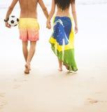 Junge schöne Paare, die entlang Strand mit Brasilien-Flagge und -fußball gehen stockbild