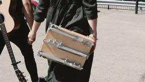 Junge schöne Paare, die herein in die Stadt zusammen, Chicago, Amerika gehen Mann, der Gitarre, Frau sketchbox hält stock footage