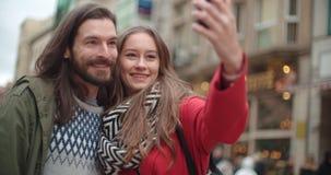 Junge schöne Paare, die selfie in einer Stadt nehmen Stockfoto