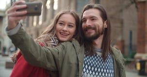 Junge schöne Paare, die selfie in einer Stadt nehmen Lizenzfreie Stockbilder