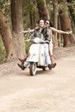 Junge schöne Paare, die Spaß mit Roller haben lizenzfreie stockfotos