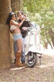 Junge schöne Paare, die Spaß mit Roller haben stockfoto