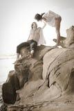 Junge schöne Paare, die am Strand flirten Stockbild