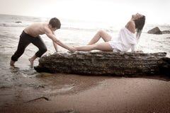 Junge schöne Paare, die am Strand flirten lizenzfreies stockfoto