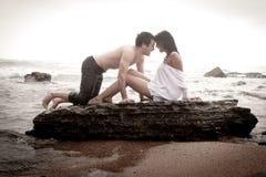 Junge schöne Paare, die am Strand flirten Lizenzfreie Stockfotografie